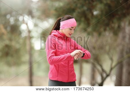 Young woman with fitness tracker on winter park background