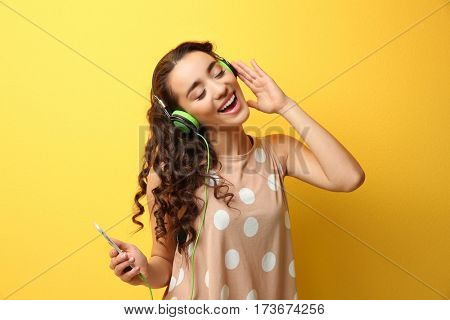 Beautiful young woman in headphones listening to music and singing on yellow background