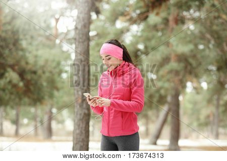Young woman wearing sportswear with mobile phone on winter park background
