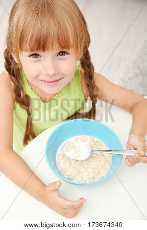 Portrait of little girl eating cornflakes with milk