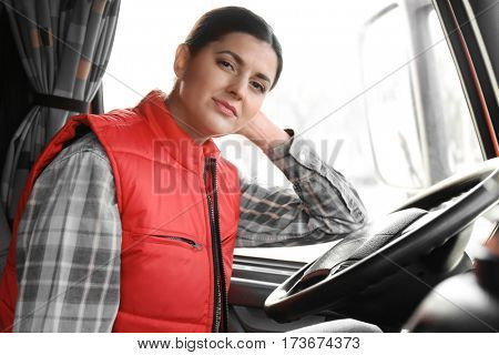 Young female driver sitting in cabin of big modern truck