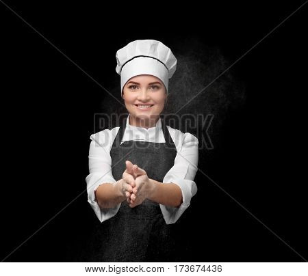 Young female chef clapping hands with flour on black background
