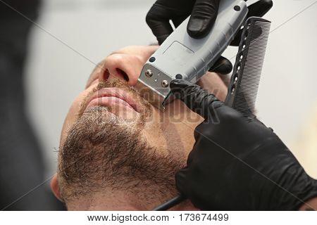 Hairdresser shaving client in barbershop