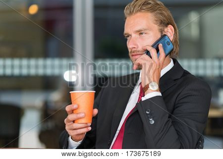 Handsome businessman talking on the phone and drinking coffee