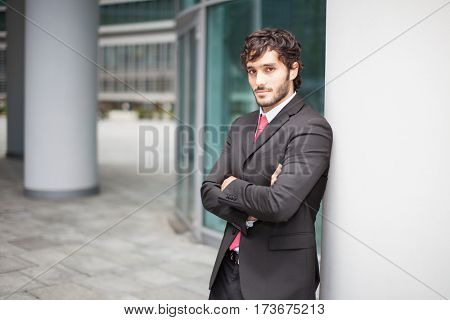 Portrait of a smiling businessman lying against a wall