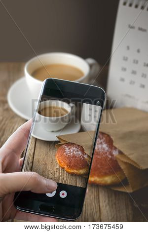 Photographing Hot Coffee and Donut on wood Background used for food ad or website promote. Snacks for people to work in the rush hour