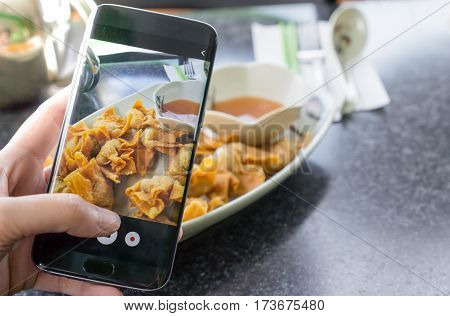 Finger pressing on smartphone for photograph chinese food in restaurant for food ad or website promote