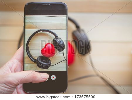 Finger pressing on smartphone for photograph Heart listen music on wooden background and copy space for love and music concept
