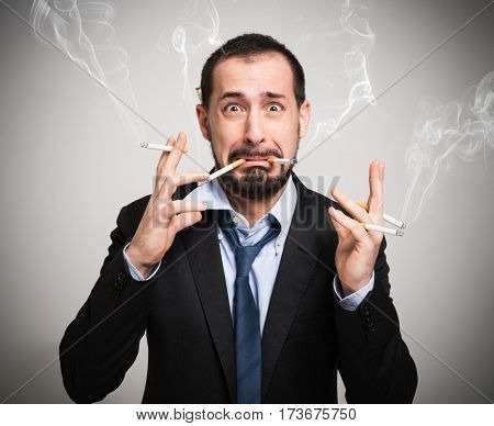 Nervous man smoking a lot of cigarettes at once