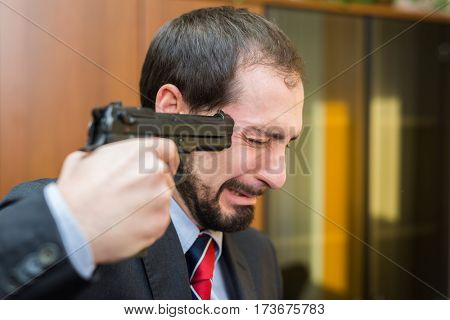 Businessman pointing a gun to his head in the office