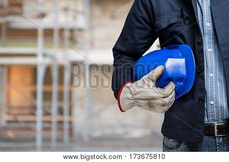 Detail of a worker holding his helmet in front of a construction site