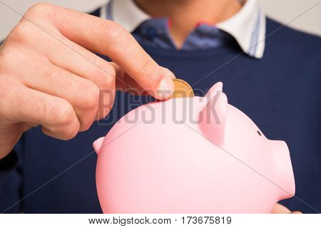 Man putting money in his piggy bank