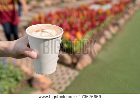 Woman holding paper cup of coffee in flower park during morning time