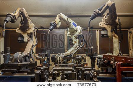 Welding robots machine in a car factory with sparks, manufacturing, industry, factory