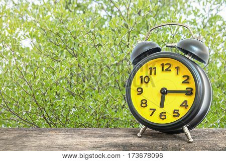 Closeup black and yellow alarm clock for decorate show a quarter past six or 6:15 a.m. on old brown wood desk on green leaves in the park textured background