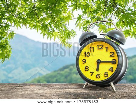 Closeup black and yellow alarm clock for decorate show a quarter past six or 6:15 a.m. on blurred leaves and mountain view background