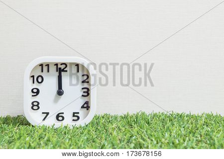 Closeup white clock for decorate in 12 o'clock on green artificial grass floor and cream wallpaper textured background with copy space