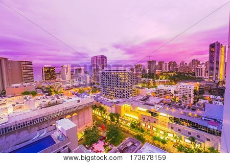 Pink light at twilight of Waikiki cityscape in Oahu island, Hawaii, United States. City night lights and nightlife concept.