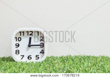Closeup white clock for decorate show a quarter past twelve or 12:15 a.m. on green artificial grass floor and cream wallpaper textured background with copy space