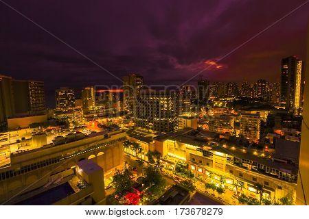 Night lights of Waikiki cityscape in Oahu island Hawaii, United States. Dark sky with moving clouds and stars. City night lights and nightlife concept.