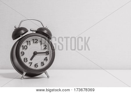 Closeup alarm clock for decorate show a quarter past seven or 7:15 a.m.on white wood desk and cream wallpaper textured background in black and white tone with copy space