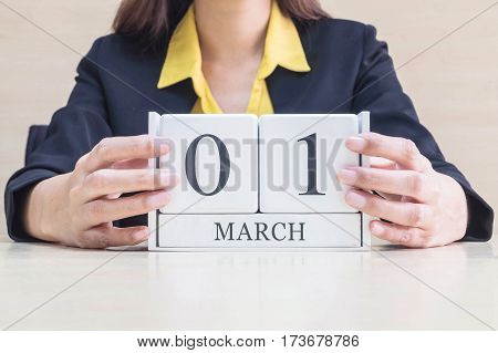 Closeup white wooden calendar with black 1 march word in blurred working woman hand on wood desk in office room selective focus at the calendar