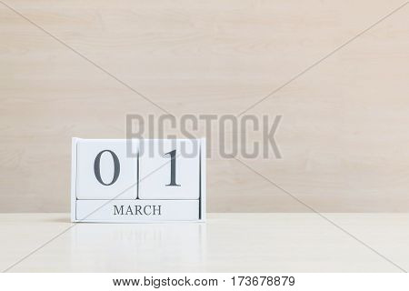 Closeup surface white wooden calendar with black 1 march word on blurred brown wood desk and wood wall textured background with copy space selective focus at the calendar