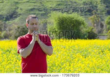 Man praying alone with his hands clasped under his chin and eyes closed.