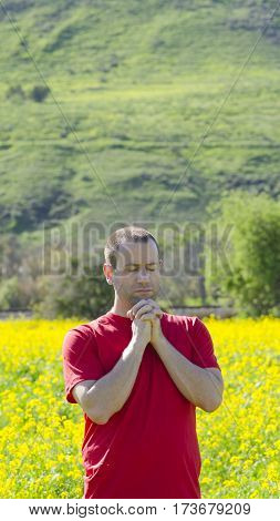 Solitude man praying with hands clasped in nature.
