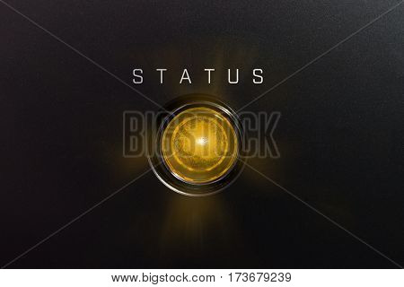 Yellow glowing warning lamp or button black panel with the words,