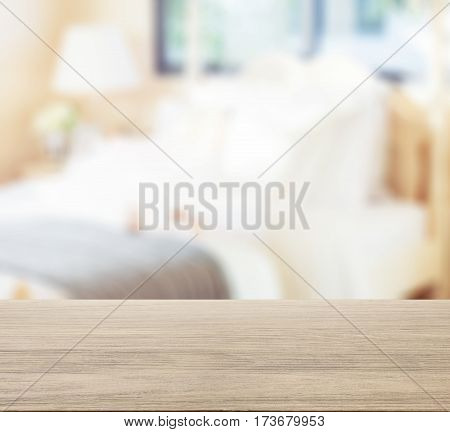 Wooden Table Top With Blur Of Cozy Bedroom With Dolls On Bed