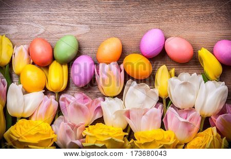 Colorful tulips and Easter eggs on old wooden background. Festive  Easter concept with copy space. Flat lay