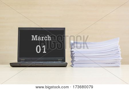 Closeup computer laptop with march 1 word on the center of screen in calendar concept and pile of work paper on wood desk and wood wall in work room textured background with copy space