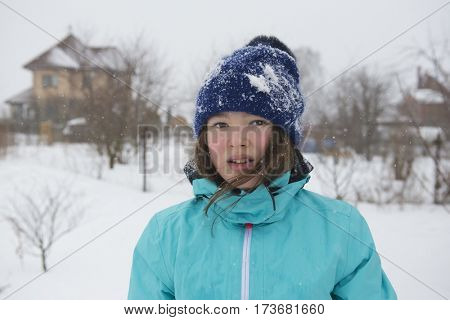Teenager girl in winter jacket and knit cap on rural landscape background.