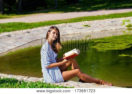Young beautiful brown haired woman sitting on stone in summer street