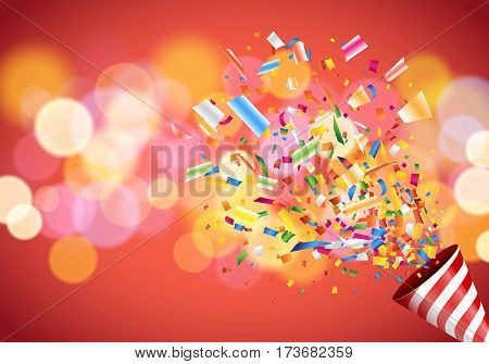 Exploding party popper on colorful defocused blurred background