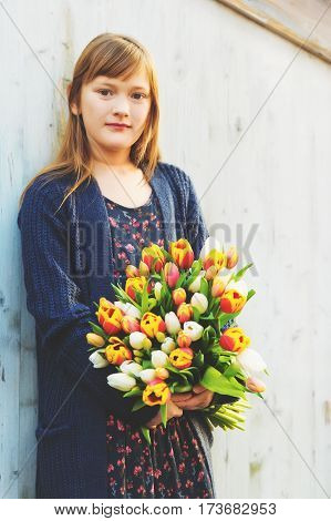 Portrait of cute 8-9 year old girl, holding bright bouquet of colorful fresh tulips, standing against white wooden background, wearing blue cardigan