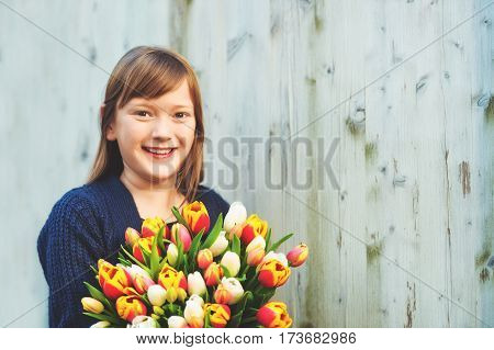 Portrait of cute 8-9 year old girl, holding bright bouquet of colorful fresh tulips, standing against white wooden background