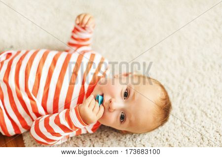 Cute 12-18 month baby boy laying on carpet floor, chewing rubber toy