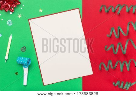 Red gift box with various party confetti streamers candle noisemakers and decoration on a colorful background. Holiday background. Flat lay