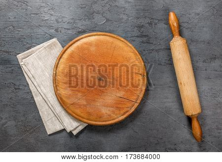 Round wooden board with a rolling pin and cloth napkin on the dark stone surface top view