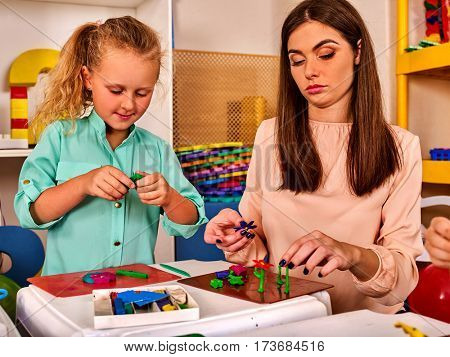 Plasticine modeling clay. Child dough play in school mold from plasticine in kindergarten .Kids knead modeling clay with hands in preschool.