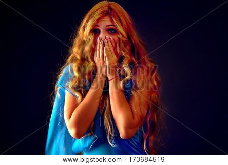 Frightened woman screaming with fear indoor at halloween night. Horror. Surprise and worried girl with tousled hair worried bawl and l covers her mouth with her hands black background.