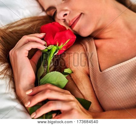 Woman sleeping in bed. Girl lying on bed with flower and dreams after date. Sleep for pregnant ladies. Top view of bedroom.