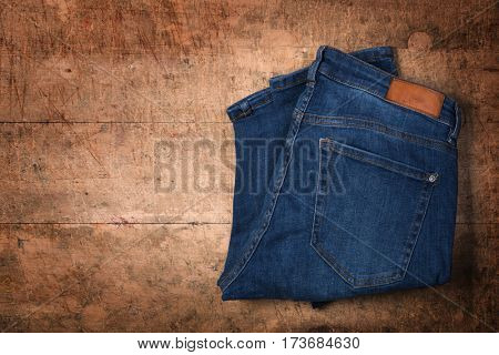 Blue jeans folded on wooden background
