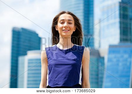 Portrait of a happy young woman in blue dress, summer street outdoors