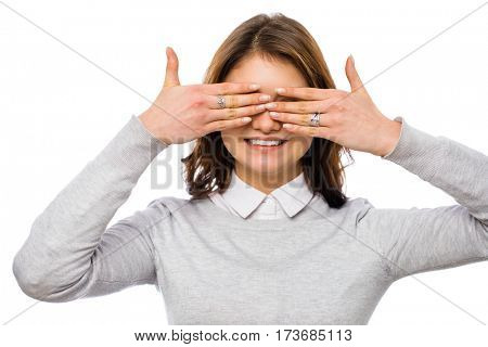 A young happy woman covers her face arms, isolated on white background