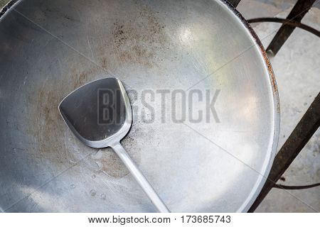 Old pan and ladle or scoop. Indoor light.