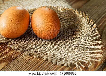 Eggs on burlap over wooden background. Macro with shallow dof