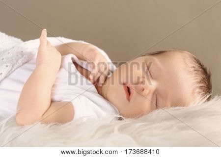 Cute little baby sleeping on soft plaid against color background